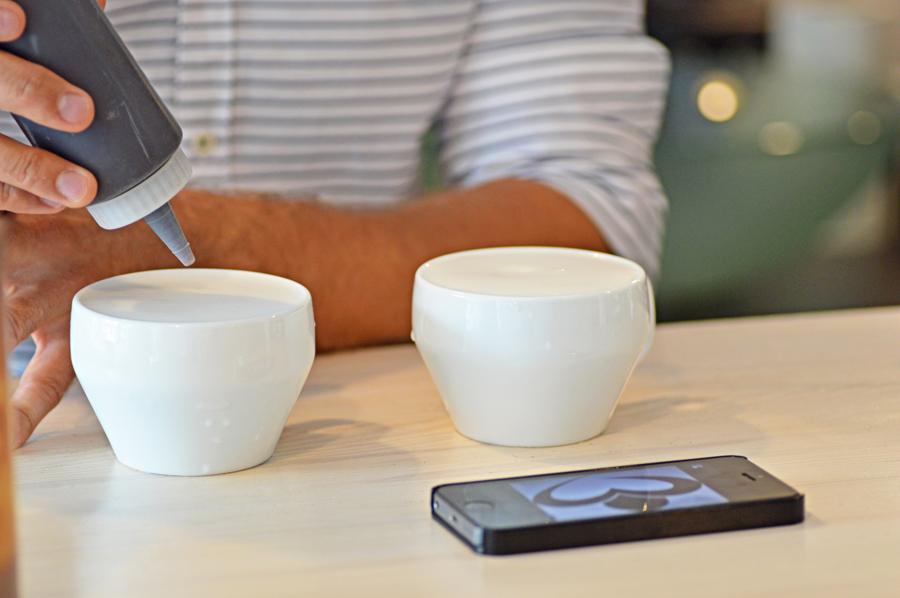 Mistrz Polski Latte Art Marcin Michalik wyczarowuje logo Perlove na kawie.
