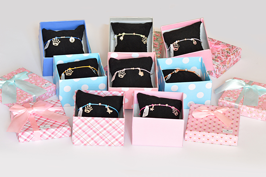 Bransoletki Queens zkolorowych sznureczków zzawieszkami ze srebra wkolorowych pudełeczkach.