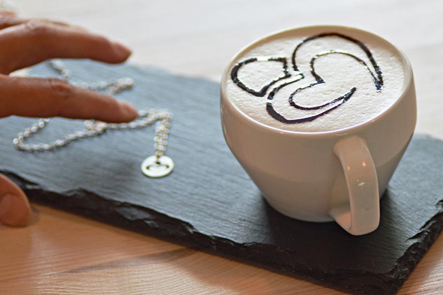Nasze logo Perlove na kawie, a wtle naszyjnik znaszym znakiem firmowym.