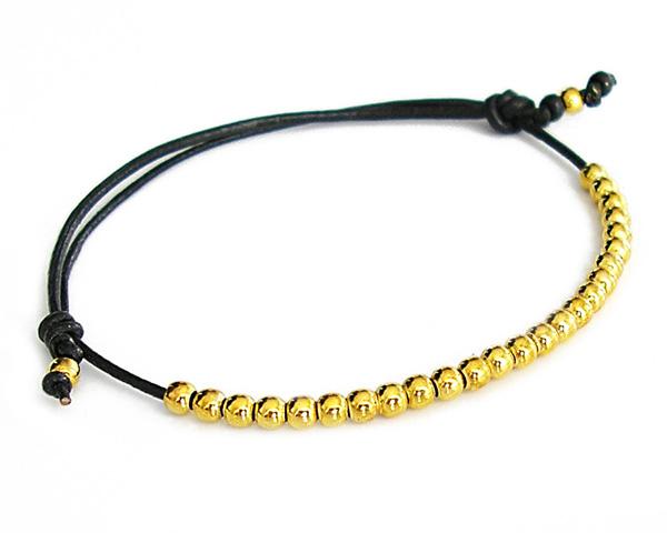 Czarna bransoletka z rzemyka ozdobiona złotymi kuleczkami.