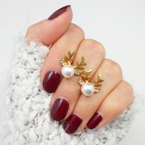 Uroczy komplet biżuterii, czyli kolczyki typu sztyfty orazzłoty łańcuszek zmotywem renifera ozdobionego perłą Swarovski.
