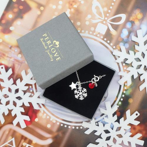 Srebrny łańcuszek ze śnieżynką i gwiazdką to biżuteria w świątecznym stylu.